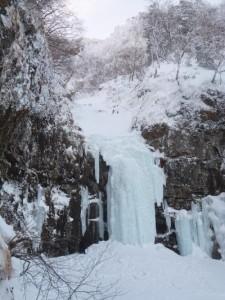 取り付きに雪がたまって小さく見える摩利支天大滝