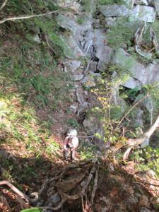 ロープが張られた急な斜面を下る