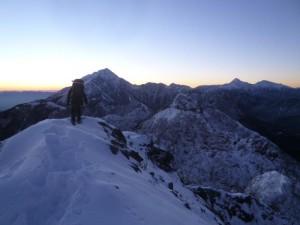 日の出に浮き上がる甲斐駒と北岳を見ながら、第一高点から下降する